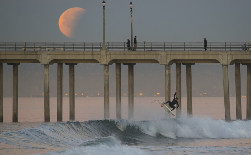 A surfer goes airborne off a wave as the super blue blood moon eclipse sets over the Huntington Beach pier.