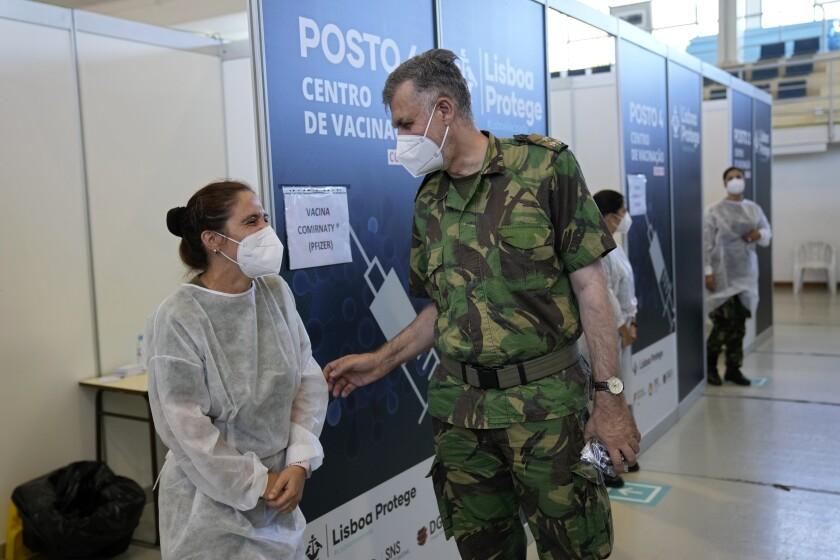 El contraalmirante Henrique Gouveia e Melo bromea con una enfermera militar durante una visita a un centro de vacunación en Lisboa, el martes 21 de septiembre de 2021. (AP Foto/Armando Franca)