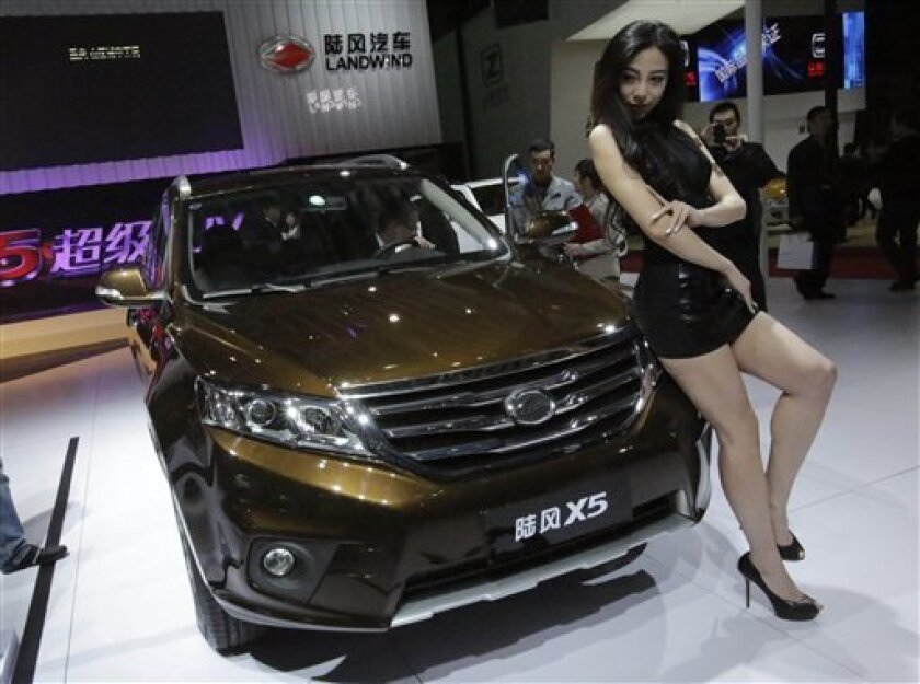 In this Saturday, April 20, 2013 photo, a model poses with the new Landwind X5 SUV at the Shanghai International Automobile Industry Exhibition (AUTO Shanghai) media day in Shanghai, China. SUV sales in China rose 20 percent last year to 2.5 million vehicles, more than double the 8 percent growth of the overall auto market, according to LMC Automotive. SUVs made up 18 percent of all vehicles sold. (AP Photo/Eugene Hoshiko)
