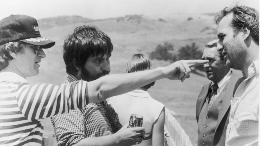Producer (and uncredited director) Steven Spielberg points as director Tobe Hooper, actors James Kar