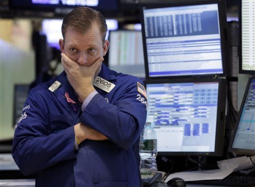 In this Thursday, Jan. 10, 2013, photo, specialist Edward Zelles works on the floor of the New York Stock Exchange. Wall Street futures were mostly flat in world markets prior to the opening bell Friday Jan. 11, 2013. (AP Photo/Richard Drew)