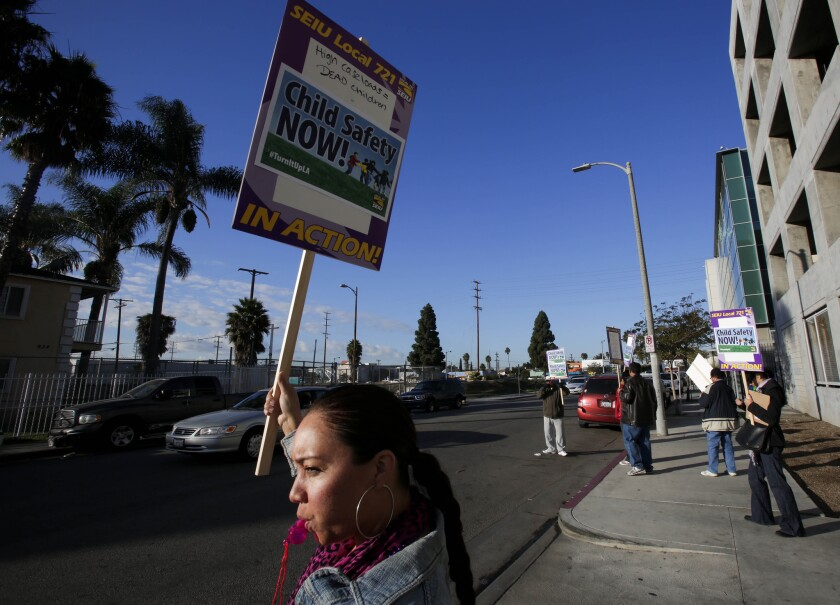 Brandie McMiller, an investigator with the Department of Children and Family Services, pickets outside DCFS offices on Vermont Avenue in South Los Angeles.