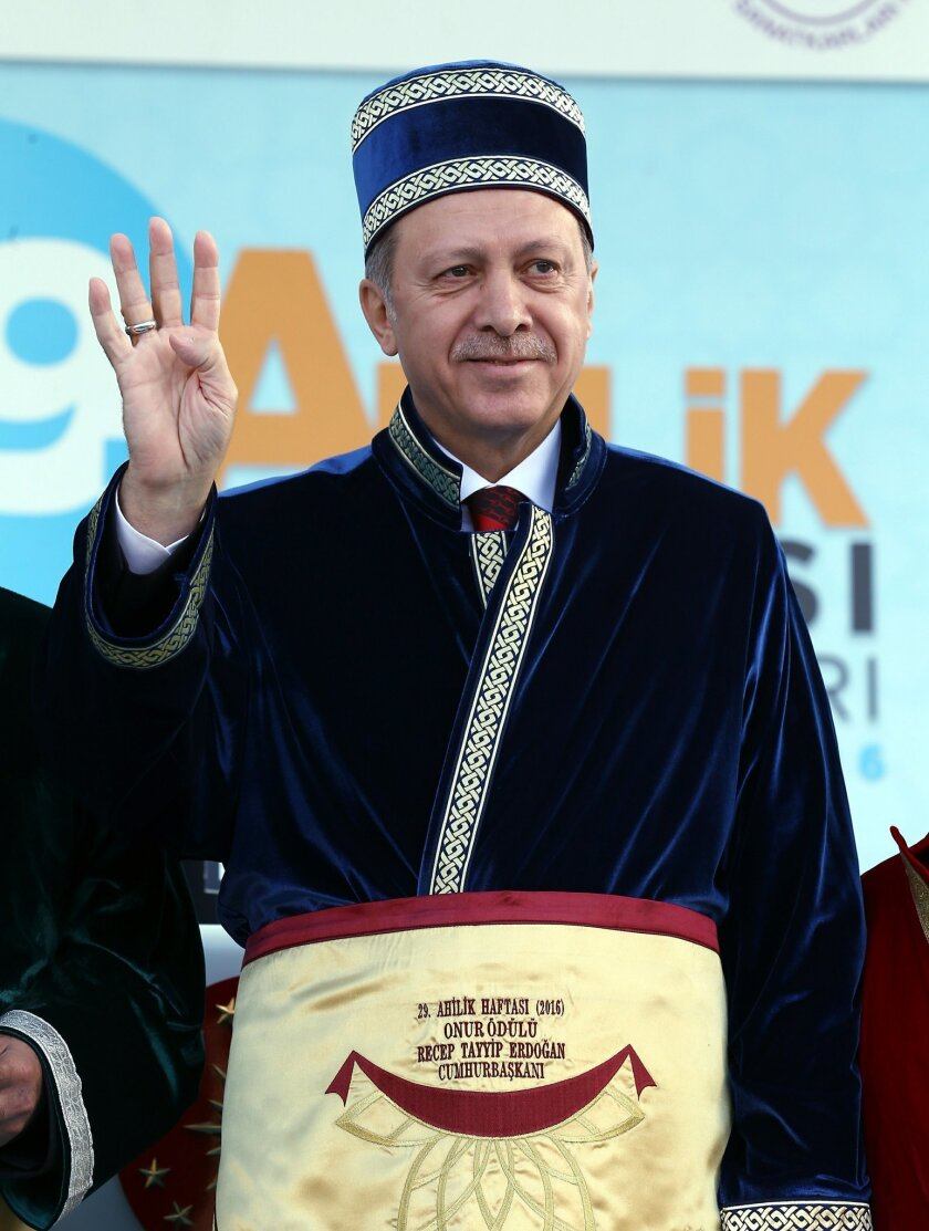 """Turkey's President Recep Tayyip Erdogan salutes in the costume of an """" ahi, """" a member of traditional Turkish artisan and merchants group, during a meeting in Central Anatolian city of Kirsehir, Turkey, Friday, May 27, 2016.(Presidential Press Service/ Pool via AP)"""