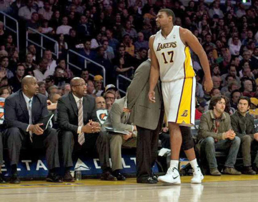 Andrew Bynum walks off the court after injuring his ankle in the first half against the Golden State Warriors.