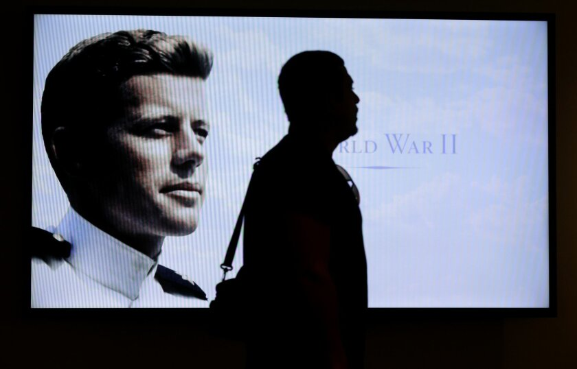 "Museum visitor Edmilson Da Cruz, of Hayward, Calif., center, is silhouetted in front of a World War II era photograph of John F. Kennedy in an exhibit  titled ""Young Jack"" at the John F. Kennedy Presidential Library and Museum, Thursday, Nov. 5, 2015, in Boston. The new exhibit is devoted to the 35"