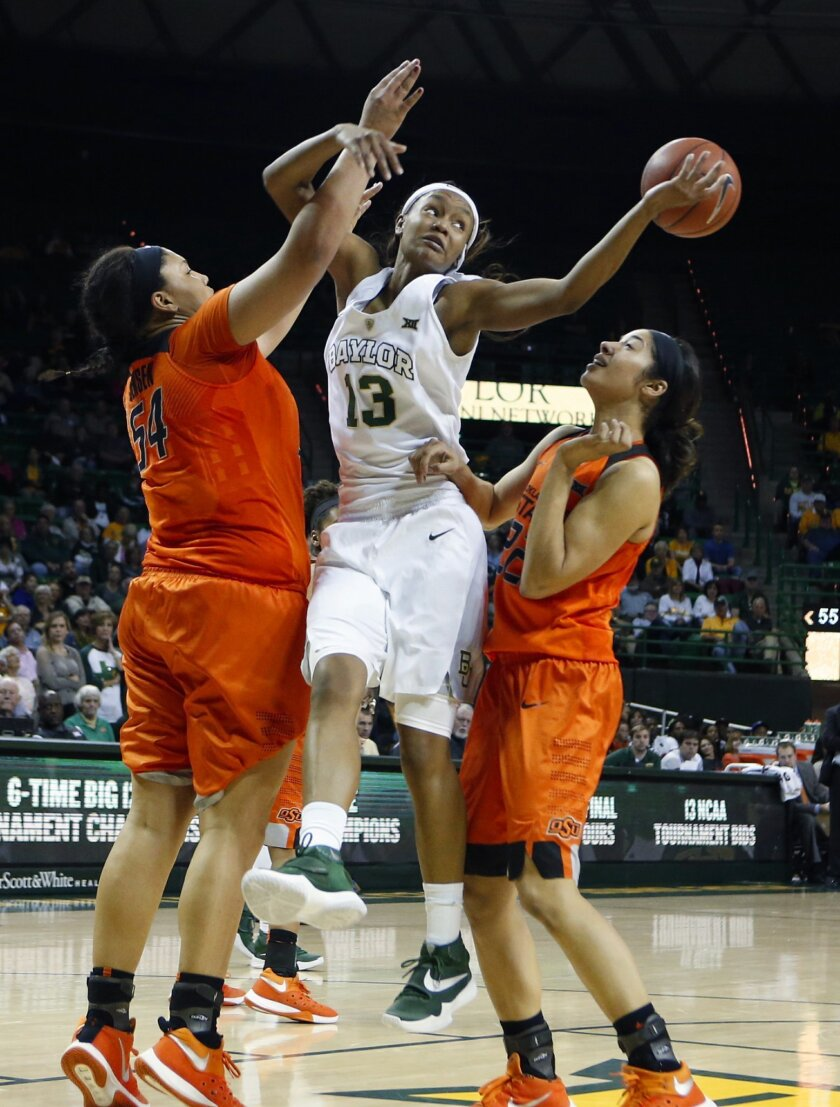 Baylor forward Nina Davis (13) reaches back for a loose ball while being defended by Oklahoma State center Kaylee Jensen, left, and guard Brittney Martin, right, in the second half of an NCAA college basketball game, Wednesday, Feb. 17, 2016, in Waco, Texas. Baylor won 66-41. (AP Photo/Jerry Larson