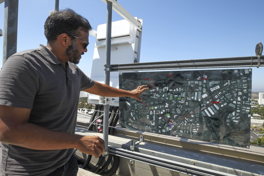 Senior Staff Engineer Vinesh Dhanaraj points to an aerial photo showing the coverage area for the Qualcomm's 5G Sub 6 Massive MIMO Gigahertz over the air antenna, left, while on the roof of the Qualcomm headquarters on Thursday, August 1, 2019 in San Diego, California.