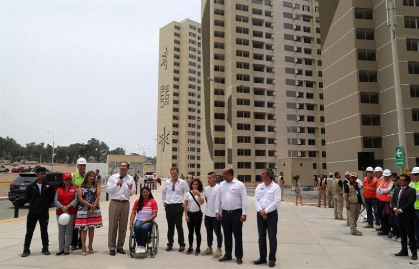 El presidente peruano, Martín Vizcarra (c), acompañado de algunos de sus ministros y algunos deportistas, habla durante un encuentro con la prensa frente a varios edificios que componen la villa de los Juegos Panamericanos de Lima 2019 este viernes, en el distrito de Villa El Salvador, en Lima (Perú). EFE