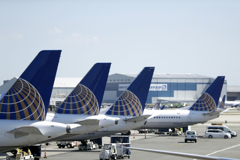 United Airlines commercial jets sit at a gate at Newark airport in Newark, N.J.