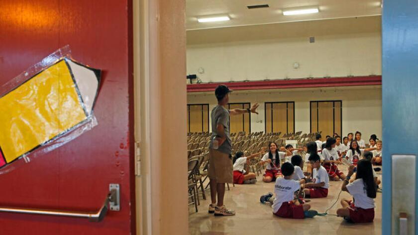 El maestro Stuart Sellz con sus estudiantes de Educación física , evitaron el calor del verano teniendo clases en la parte de atrás del auditorio en lugar de hacerlo afuera de Lawrence Middle School en Chatsworth.