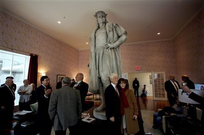 "Leaders of the Italian-American community, civil servants from New York and Italy, including police and sanitation workers and other guests, stand in what is known as the living room created by artist Tatzu Nishi that surrounds Gaetano Russo's 1892 sculpture of Christopher Columbus 75 Feet Above Columbus Circle Sunday, Oct. 7, 2012, in New York. The art installation ""Tatzu Nishi: Discovering Columbus,"" which brings people to eye level with the Columbus statue, became part of an annual wreath laying ceremony that celebrates Columbus Day. Posing center right for a photograph is Mario Gabelli, Grand Marshall of the 2012 Columbus Day parade, and Natalia Quintavalle, Consul General of Italy in New York. (AP Photo/Craig Ruttle)"