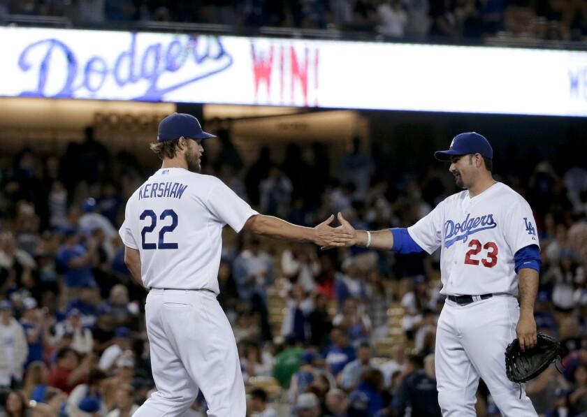 El lanzador de los Dodgers de Los Ángeles, Clayton Kershaw, (izq) choca las manos con el primera base Adrián González el final de un partido contra los Filis de Filadelfia.