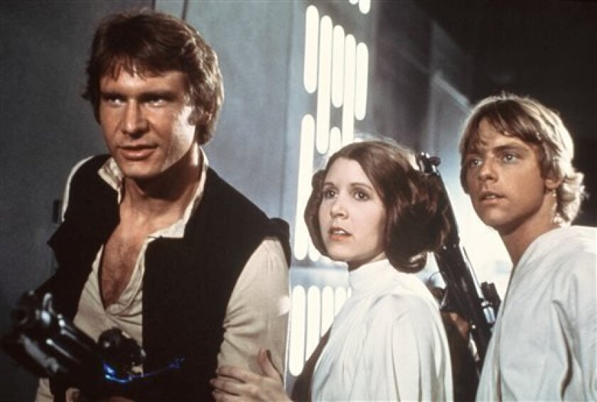 "This publicity film image provided by 20th Century-Fox Film Corporation shows, from left, Harrison Ford as Han Solo, Carrie Fisher as Princess Leia Organa and Mark Hamill as Luke Skywalker in a scene from the ""Star Wars"" movie released by 20th Century-Fox in 1977."