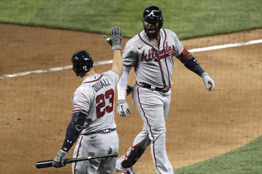 Atlanta Braves' Marcell Ozuna, right, is met by Adam Duvall (23) after scoring on a solo home run during the seventh inning of the team's baseball game against the Miami Marlins, Saturday, Aug. 15, 2020, in Miami. (AP Photo/Lynne Sladky)