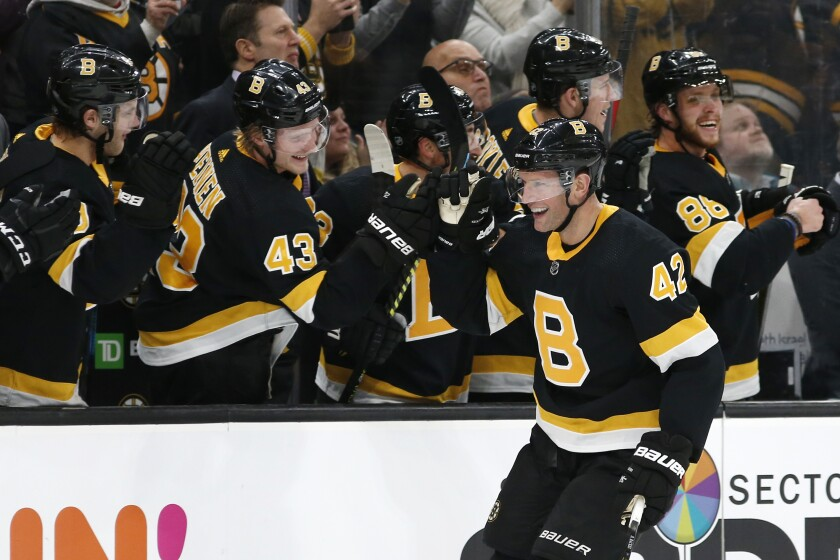 Boston Bruins' David Backes is congratulated by teammates at the bench after scoring against the Montreal Canadiens during the third period of an NHL hockey game Sunday, Dec. 1, 2019, in Boston. (AP Photo/Winslow Townson)
