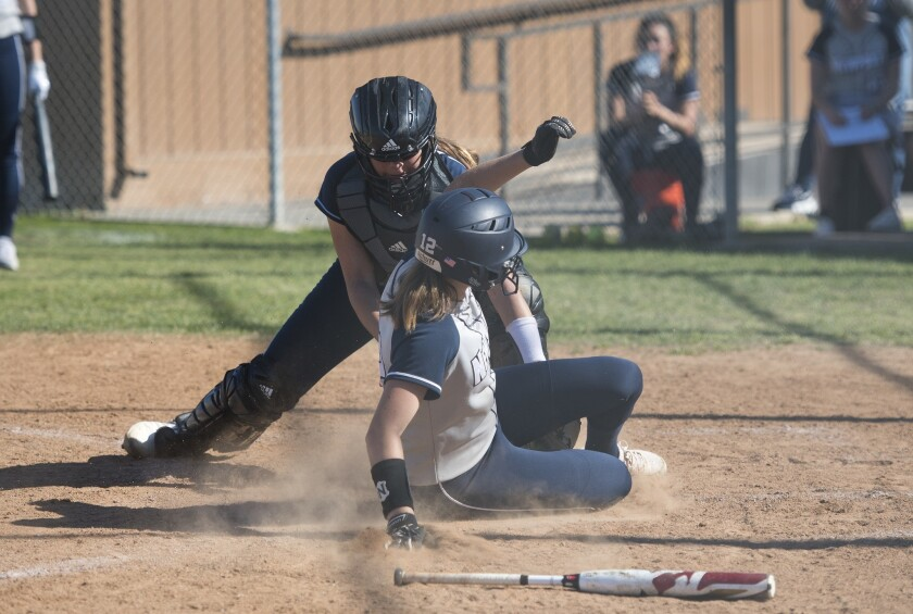 Newport Harbor's Eliana Gottlieb slides safely into home plate, avoiding the tag from Corona del Mar