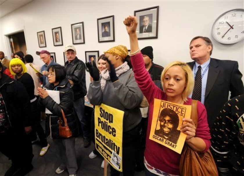 Gabrielle Rae holds a photo of Oscar Grant while attending a BART board of directors meeting on Thursday, Jan. 8, 2009, in Oakland, Calif. Speakers criticized the transit agency for its handling of a New Year�s Days incident involving a BART police officer who shot and killed Grant, an unarmed 22