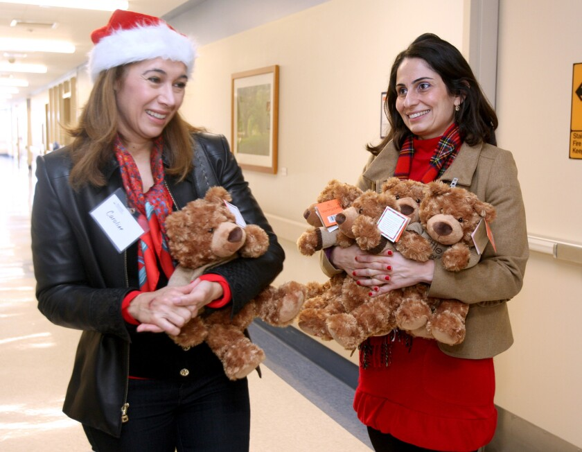 Volunteer Caroline Tufenkian, left, and Glendale Adventist Medical Center marketing director Alina Dersarkissian, right, help pass out teddy bears to patients for the holidays, at GAMC in Glendale on Wednesday, Dec. 23, 2015. Sixty stuffed bears from Bloomingdale's were handed out to patients throughout the hospital.