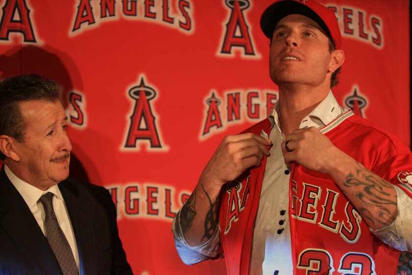 Angels owner Arte Moreno, left, watches outfielder Josh Hamilton put on his jersey during a news conference to introduce the 2010 American League MVP on Dec. 15, 2012.