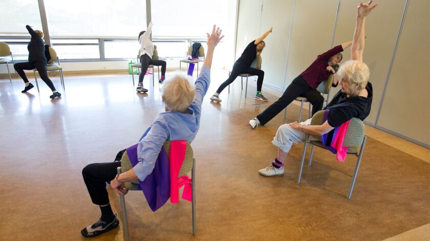 Kathryn Rollins teaches a chair standing class at the OASIS Senior Center on December 14, 2017.