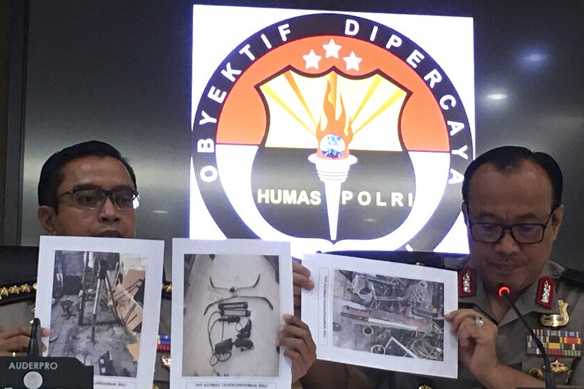 Dedi Prasetyo, right, national police spokesman in Indonesia, helps display photos of confiscated items during a news conference Oct. 17 in Jakarta.