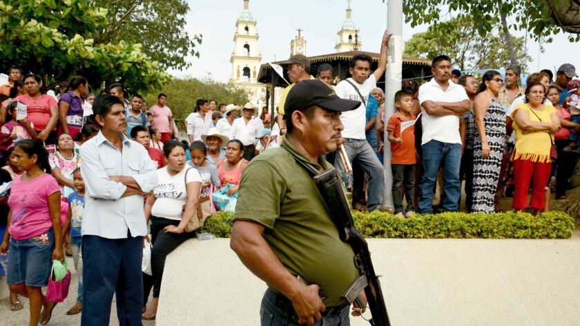 A security officer stands guard at a campaign appearance by a Senate candidate in San Luis Acatlan, Guerrero state.