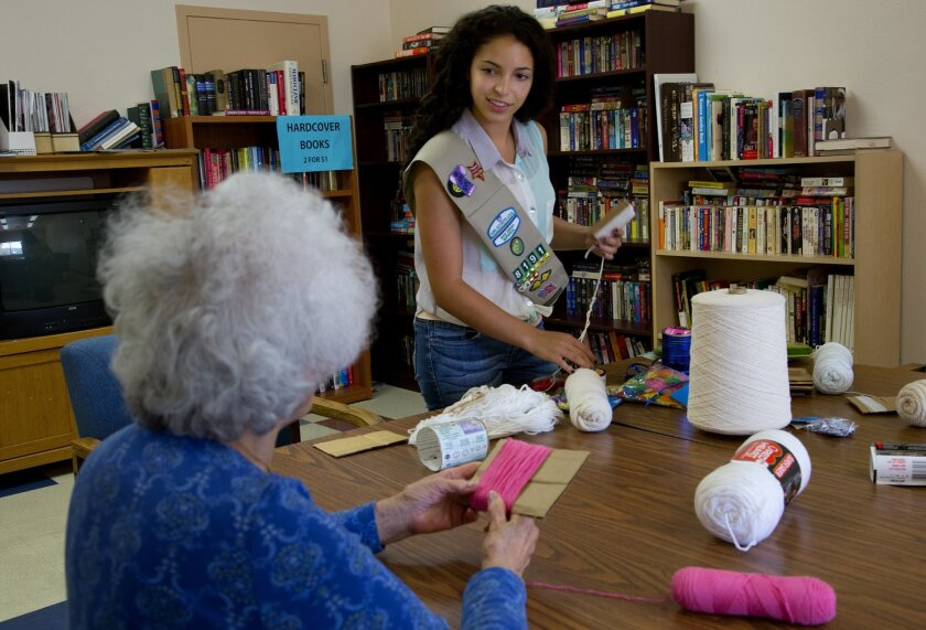 Elisa Lupin-Jiminez conducts her craft class at Ed Brown Senior Center.  During this class Elisa helps Pearl Hom work on creating a small doll from yarn.