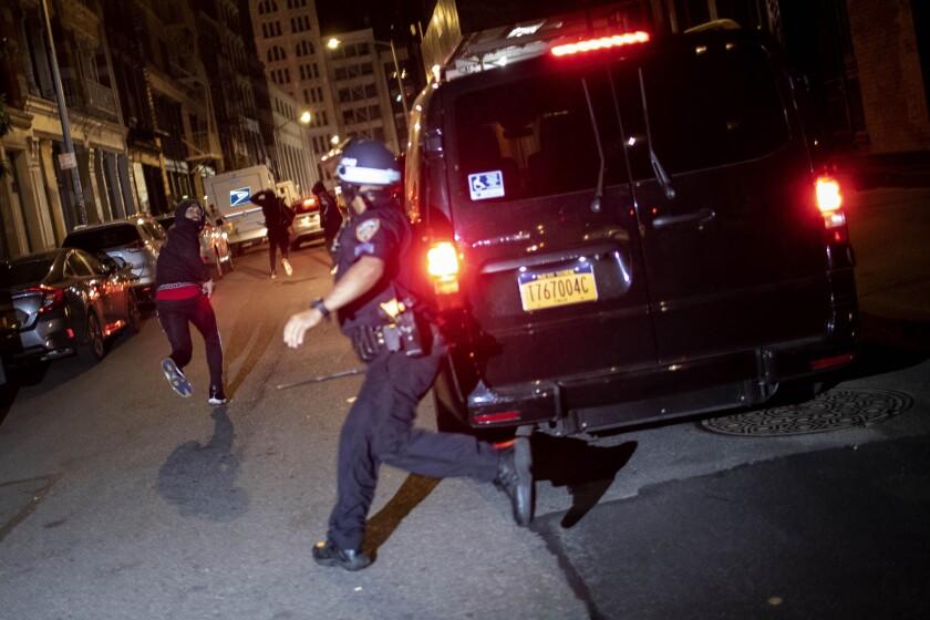 ARCHIVO - En esta foto de archivo del 1 de junio de 2020, un manifestante huye perseguido por la policía en Nueva York. El video aterrador de un agente de policía de Chicago que mata de un tiro a un chico de 13 años vuelve a echar luz sobre los criterios que rigen las persecuciones a pie. (AP Foto/Wong Maye-E, File)