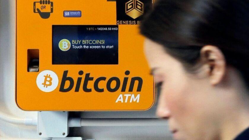 A woman walks past a Bitcoin ATM in Hong Kong on Dec. 21, 2017.
