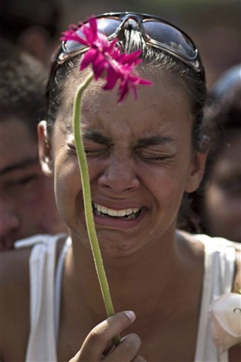 A women cries while attending the funeral of one of 12 children killed the day before in a school shootout in Rio de Janeiro, Brazil, Friday April 8, 2011. Brazilian families began burying the children gunned down in the halls of their elementary school Thursday. Ten girls and two boys between the ages of 12 and 15 were killed by 23-year-old Wellington Oliveira, who shot and killed himself after being confronted by police. (AP Photo/Felipe Dana)