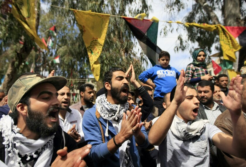 Palestinian refugees, including some who fled from Yarmouk camp in Damascus, chant slogans to show their solidarity with thousands of besieged Palestinians in Yarmouk which was overrun by Islamic State militants last week, during a demonstration in the Ein el-Hilweh camp near the southern city of Sidon, Lebanon, Lebanon, Friday, April 10, 2015. The Palestine Liberation Organization says it won't be drawn into military action against the Islamic State group in Yarmouk. (AP Photo/Mohammed Zaatari)