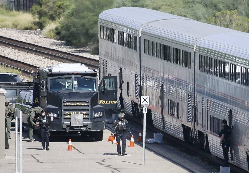 A Tucson Police Department SWAT truck is parked near the last two cars of an Amtrak train in downtown Tucson, Ariz., Monday, Oct. 4, 2021. The Pima County Medical Examiner's Office, in Tucson said Thursday, Oct. 7, 2021 that 26-year-old Darrion Taylor was identified as the gunman who shot and killed Drug Enforcement Administration Special Agent Michael Garbo and wounded two other DEA agents and a Tucson police officer before being shot killed by other officers.(Mamta Popat/Arizona Daily Star via AP)