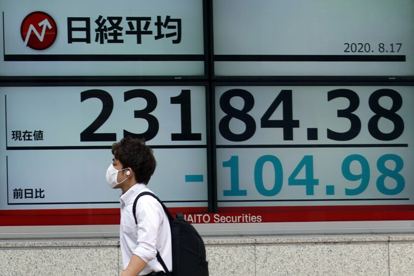 A man walks past an electronic stock board showing Japan's Nikkei 225 index at a securities firm in Tokyo Monday, Aug. 17, 2020. Japanese stocks sank while other Asian markets gained Monday after Japan reported a record economic contraction as the coronavirus pandemic weighed on retailing, investment and exports. (AP Photo/Eugene Hoshiko)