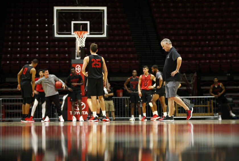 SDSU coach Brian Dutcher, right, looks on as the team practiced last month at Viejas Arena.