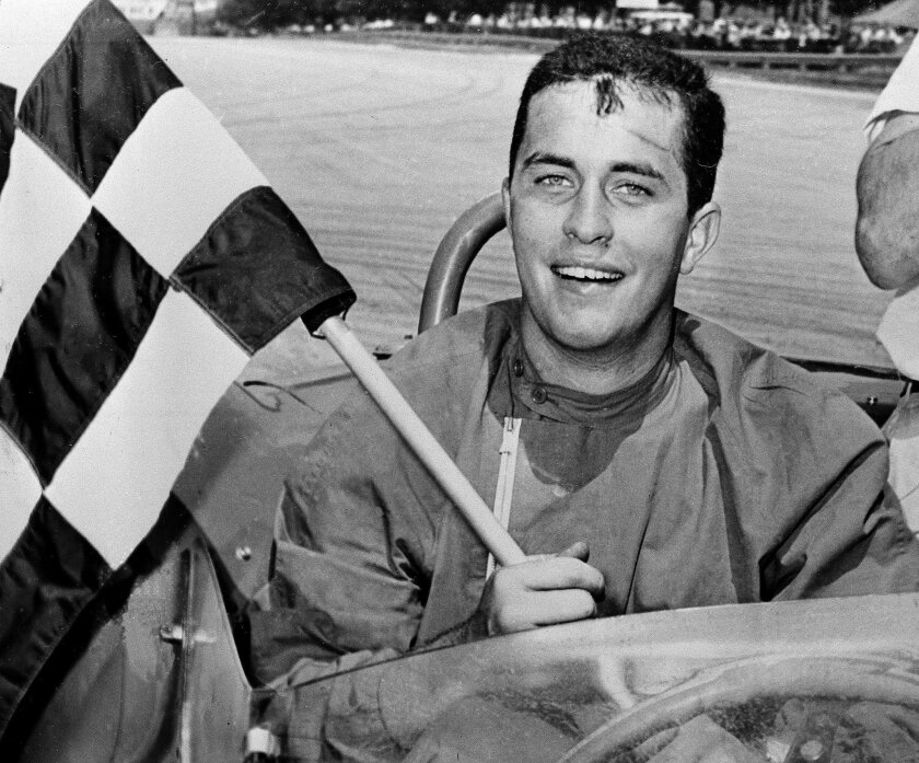 FILE - In this June 19, 1961, file photo, Roger S. Penske displays the checkered flag after he won the 100-mile race in the June sprints of Road America in Elkhart Lake, Wisc. With all the hoopla surrounding the 100th Indianapolis 500, Roger Penske has a celebration of his own going — the 50th anni
