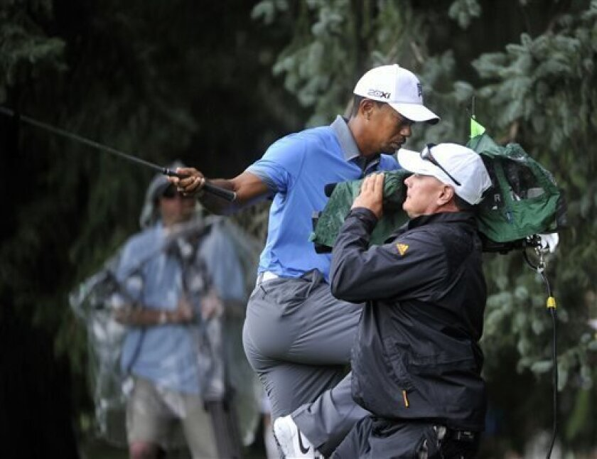 Tiger Woods trips over a TV cameraman as he tries to see is ball in the rough at the 18th hole, during the second round, at the WGC Bridgestone Invitational golf tournament, at Firestone Country Club in Akron, Ohio, Friday, Aug. 2, 2013. Woods parred the hole, shot a nine-under par 61 and tied the tournament single-round record. (AP Photo/Phil Long)