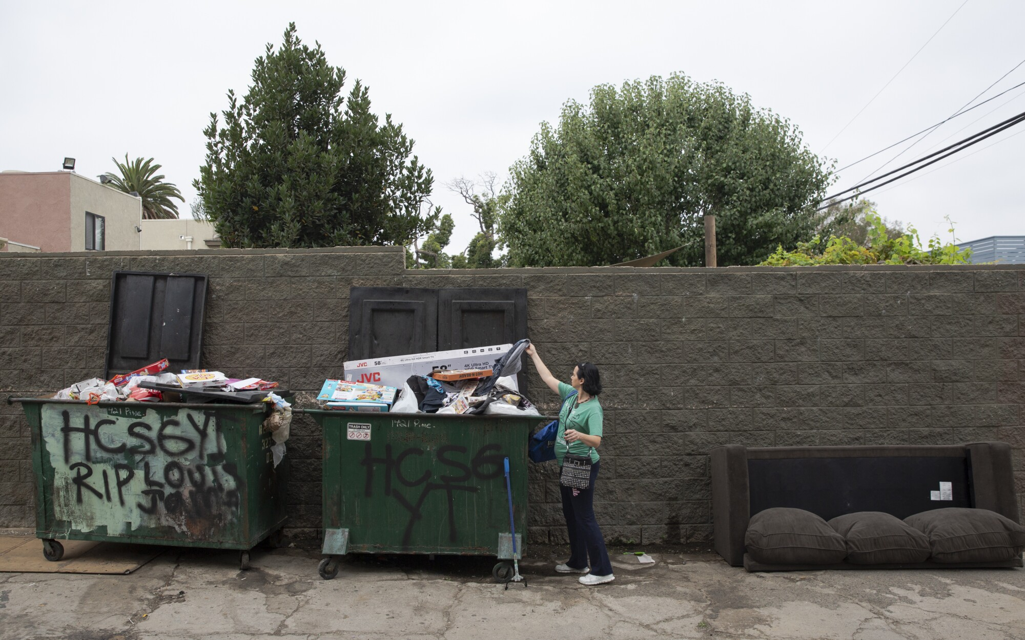 Amber Elizabeth Stevens reaches into a dumpster for salvageable items.