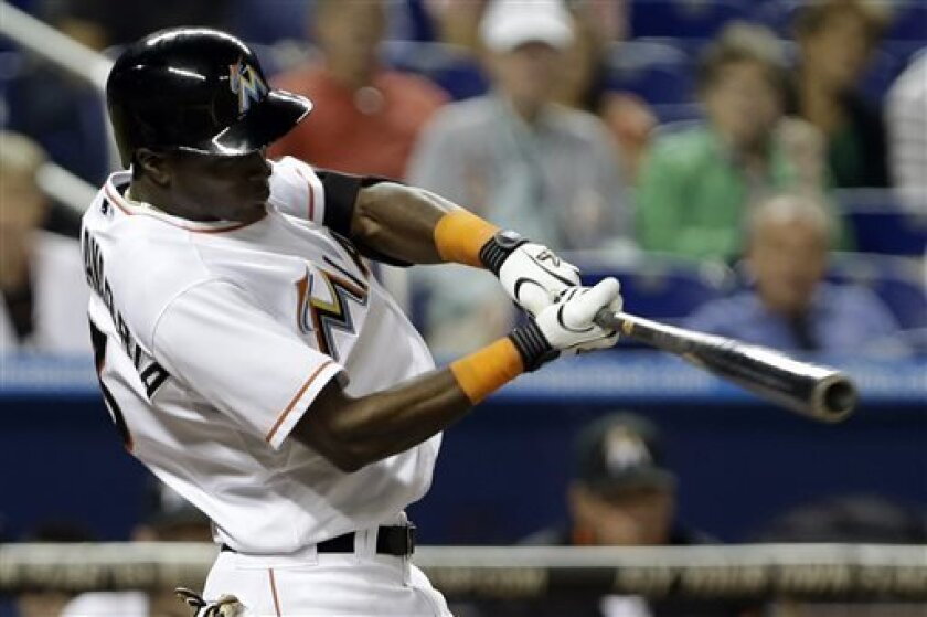 Miami Marlins' Adeiny Hechavarria hits a three-run home run during the fourth inning of a baseball game against the Washington Nationals, Tuesday, April 16, 2013, in Miami. Greg Dobbs and Justin Ruggiano scored on the play. (AP Photo/Wilfredo Lee)