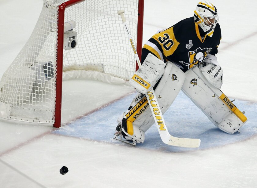 A camera lens bounces across the ice beside Pittsburgh Penguins goalie Matt Murray during the first period in Game 2 of the NHL hockey Stanley Cup finals between the Penguins and the San Jose Sharks on Wednesday, June 1, 2016, in Pittsburgh. (AP Photo/Gene J. Puskar)