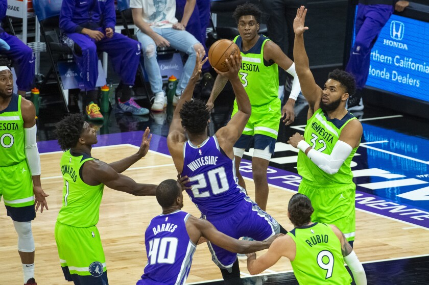 The Minnesota Timberwolves center Karl-Anthony Towns (32) defends the basket as Sacramento Kings center Hassan Whiteside (20) shoots during the first quarter of an NBA basketball game in Sacramento, Calif., Tuesday, April 20, 2021. (AP Photo/Randall Benton)