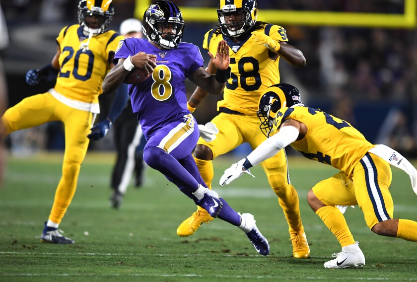 Ravens quarterback Lamar Jackson picks up a big gain against the Rams at the Coliseum.