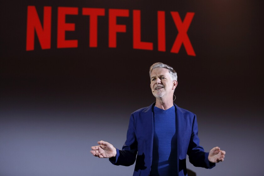 Reed Hastings with Netflix logo in the background