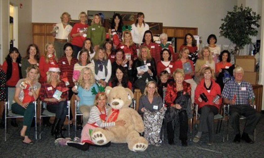 Friends of San Pasqual Academy volunteers display some of the wonderful items that were donated and collected by many caring individuals for a Holiday Party for the foster teens of San Pasqual Academy. The party was held at the school and greatly enjoyed by the foster teens. Pictured are the volunteers that helped with the festivities.
