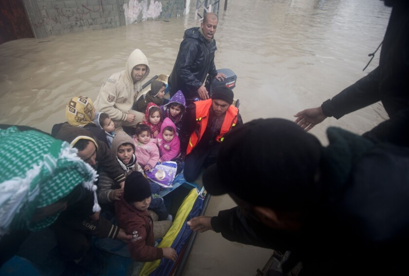 Palestinian civil defense volunteers help flooded-out residents reach safety in Gaza City on Saturday.