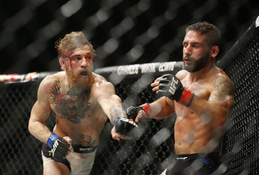 Conor McGregor (izq) lanza un derechazo a Chad Mendes(der) en el duelo de UFC 189.