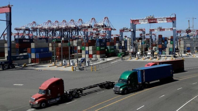 Trucks travel along a loading dock on Aug. 22, 2018, in Long Beach, Calif. The Commerce Department on Oct. 26 said the U.S. economy grew at a 3.5 percent annual rate in the July-September quarter.