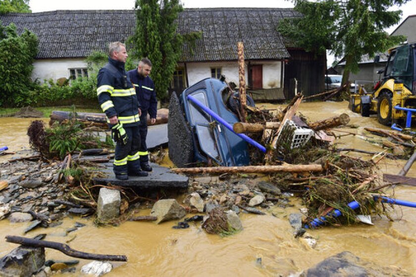 Firefighters look on a car trapped in a flooded area in Brevenec, the part of the village of Sumvald in the Olomouc region, Czech Republic, Monday, June 8, 2020. At least one person died, another is missing and dozens were rescued amid flash flooding in the northeastern Czech Republic. (AP Photo via CTK/Ludek Perina)