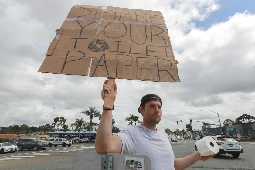 Encinitas resident Jonny Blue, 33, who is a physical therapist, makes a request for toilet paper so that he can in turn give it to drivers who need it while standing at the intersection of Encinitas Boulevard and El Camino Real on Saturday.