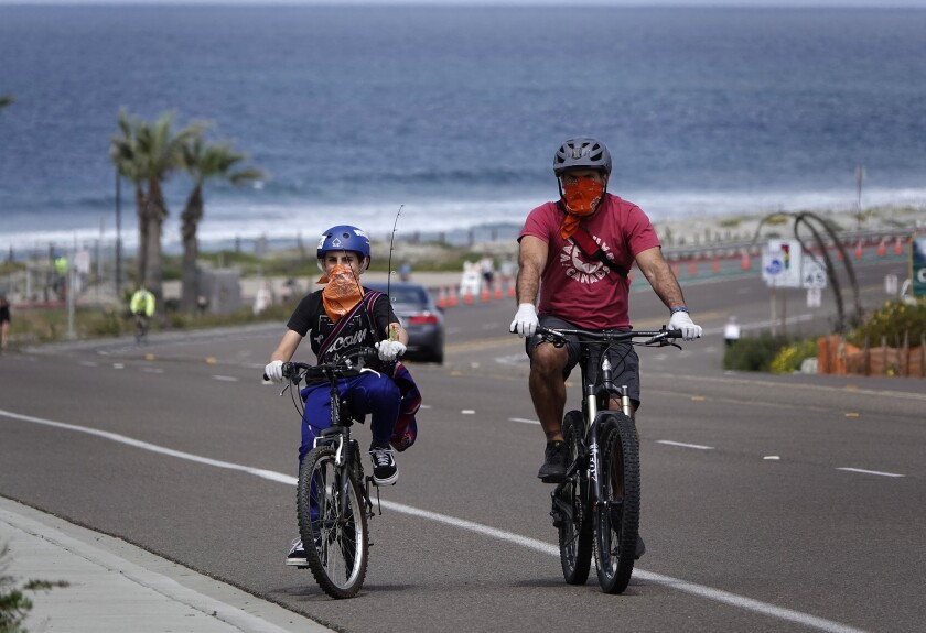 Neal Tricarico and his son Anthony wear face coverings while riding bicycles along Coast Highway in Encinitas in April.