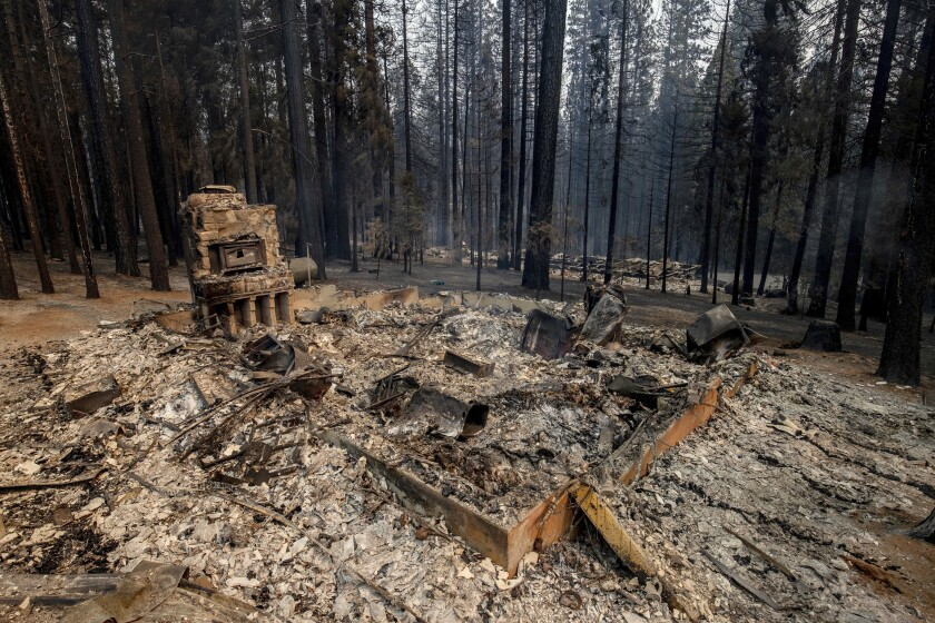 The remnants of a foundation is all this left after a property was destroyed by the Caldor Fire in Grizzly Flats, Calif., on Tuesday, Aug. 17, 2021. (AP Photo/Ethan Swope)
